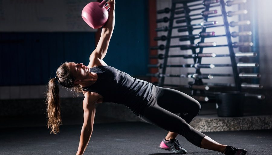 Woman athlete exercising with kettlebell indoors