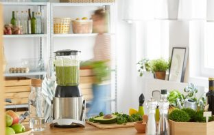 blender on the counter with greens superfood powder in the smoothie