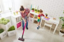 mother and daughter using a cordless vacuum cleaner to clean the kitchen floor