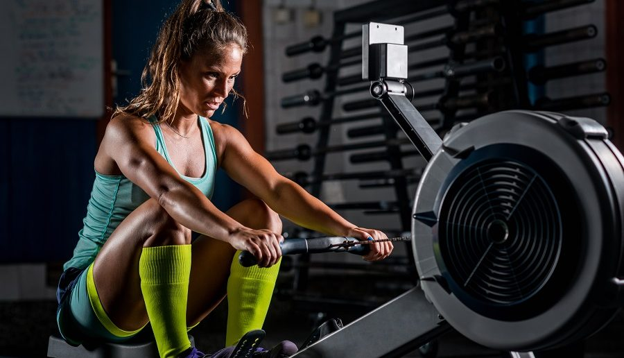 Woman athlete exercising on the top rowing machine for your home gym