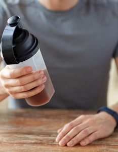 sport, healthy lifestyle and people concept - close up of man wearing fitness tracker with jar and bottle preparing protein shake
