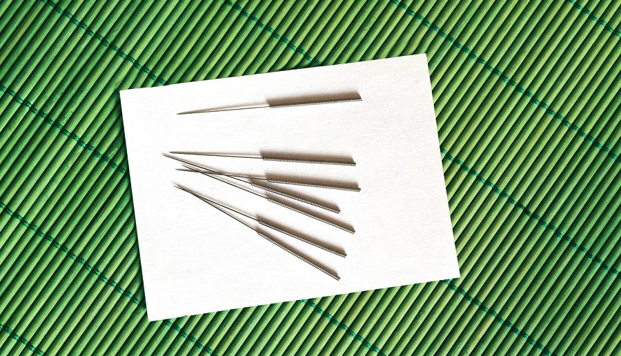 acupuncture needles on a white substrate and a bamboo napkin