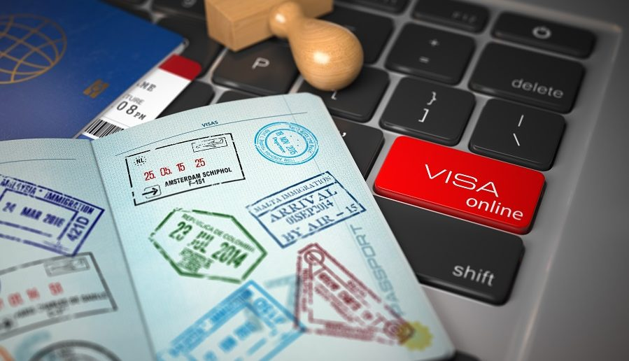 Visa online application concept. Open passport with visa stamps with airline boarding pass tickets and stamper on the computer keyboard. 3d illustration