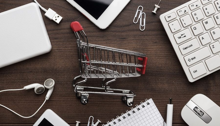 shopping online concept. small red trolley and gadgets on the table showing how google shopping works