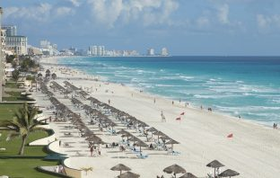 A view along the beach of the Caribbean Sea and hotels in Cancun, Mexico