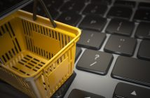 E-commerce, online shopping, internet purchases concept. Yellow shopping basket on computer laptop keyboard, 3d illustration